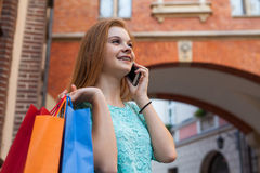 Young girl with colorful shopping bags calling her friend. Royalty Free Stock Images
