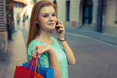 Young girl with colorful shopping bags calling her friend. Stock Photos