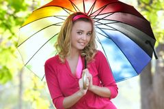 Young girl with colorful umbrella on nature Stock Images