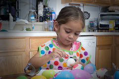 Young girl coloring Easter eggs with color in hand stock photos