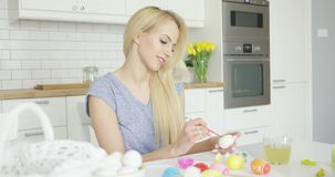 Young girl coloring eggs for holiday stock video