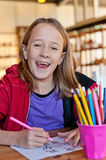 Young girl colouring, smiling. To camera Royalty Free Stock Photography
