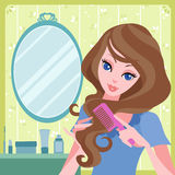 Young girl combing her hair Stock Image