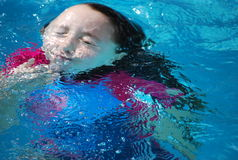 Young girl coming up from underwater in a pool. Stock Photo