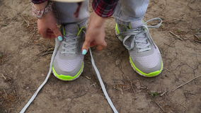 Young girl commits an outdoor walk and stopped to tie his shoelaces on sneakers stock footage