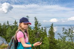 Young girl with compass on the hill top in Koli National Park. Finland stock photo