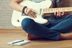 Young girl composes music. Young girl playing the guitar and composes music Stock Photo