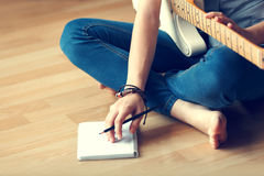 Young girl composes music. Young girl composes music while sitting on the wooden floor Royalty Free Stock Photos