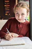 Young girl composing music. Looking across table, girl with pencil in hand Royalty Free Stock Images