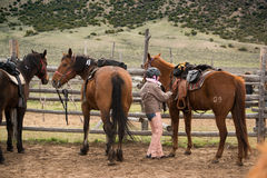 Young girl in corral saddling her horse for a trailride Royalty Free Stock Image