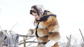 Young girl correcting winter clothes near fence and looking aside 4K.  stock video
