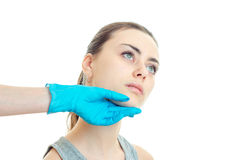 A young girl at a cosmetologist who checks her face with his hand in a blue glove close-up. On white background Royalty Free Stock Photo