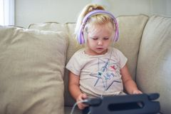 Child with headphones sitting on couch alone with laptop tablet royalty free stock images