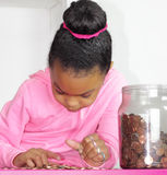 Counting my spare coins. Young girl counting the change in her savings bank.  Focus on the eyes Stock Photo