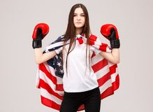 A young girl, covered with a American flag and dressed in boxing gloves. stock photo