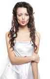 Young girl covered with bed sheet giving a kiss Royalty Free Stock Image