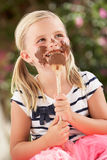 Young Girl Covered In Chocolate Licking Spoon Stock Photos
