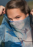 Young girl covered her face with a blue scarf Stock Photos