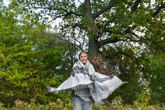 The young girl covered with a plaid dances in the autumn wood. Royalty Free Stock Image