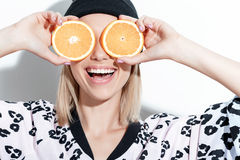 Young girl covering her eyes with oranges Royalty Free Stock Photography