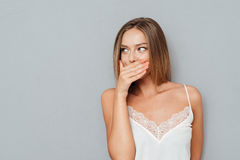 Young girl covering her mouth and looking away isolated Stock Image