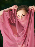 Young girl covers face like arabic woman Royalty Free Stock Photo