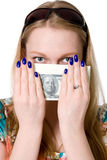 A young girl covers her face with a pack of dollars. Stock Photo