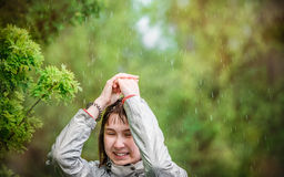 Young girl covers her head with her hands from the rain Stock Photos