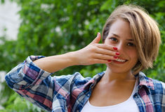 Young girl covers her smile with his  hand. Young girl covers her smile with his right hand Stock Photography