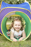 Young Girl Crawling Through Play Equipment Stock Image