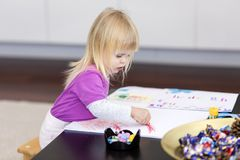 Little girl draws on the paper. Stock Photo