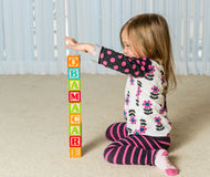 Young girl creating Obamacare tower from wood blocks. Young female toddler building a tower of wooden blocks at home spelling Obamacare Royalty Free Stock Photo
