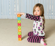 Young girl creating Obamacare tower from wood blocks. Young female toddler building a tower of wooden blocks at home spelling Obamacare Stock Photos