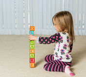 Young girl creating Obamacare tower from wood blocks. Young female toddler knocking down a tower of wooden blocks at home spelling Obamacare Stock Photography