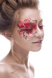 A young girl with a creative makeup in the form of a red-gold flower on her eye. Beautiful model in the image of a spring flower. Royalty Free Stock Image
