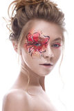 A young girl with a creative makeup in the form of a red-gold flower on her eye. Beautiful model in the image of a spring flower. Photo is taken in a studio Stock Photography