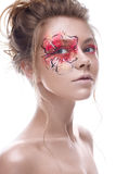 A young girl with a creative makeup in the form of a red-gold flower on her eye. Beautiful model in the image of a spring flower. Royalty Free Stock Photos