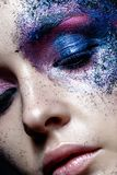 Young girl with creative makeup with texture. Beautiful model with sparkles. Trendy purple smokies. Beauty of face, shining skin. Royalty Free Stock Photography