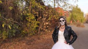A young girl with a creepy make-up in the form of a skull on a empty road. A young girl with a creepy make-up in the form of a skull on her face in a wedding stock video footage
