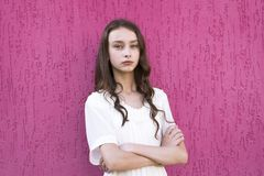 Young girl with crossed arms. Long-haired beautiful young woman with crossed arms. Girl in stylish dress posing outdoors isolated on pink background stock photography