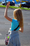 Young girl crossing the street. Alone with hand up Stock Images