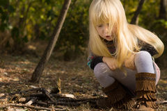 Young Girl Crouching Outdoors in Autumn Stock Photography