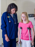 Young girl on crutches with nurse Stock Images