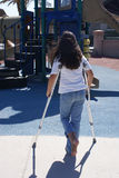Young Girl with Crutches at Playground. Young girl looking at the playground unable to play because she has injured her foot or ankle Stock Images