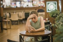 Young girl is crying along in a cafe closing her face with her hand. Teenager broke up with boyfriend. Young girl is crying along in cafe closing her face with stock photo