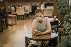 Young girl is crying along in a cafe closing her face with her hand. Teenager broke up with boyfriend royalty free stock images