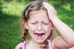 Young girl crying because of headache Stock Image