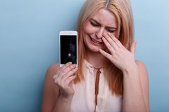 Young girl, crying holding a broken mobile phone in hand. Close-up. On a blue background. Young blonde girl, European appearance, emotionally crying holding a stock image