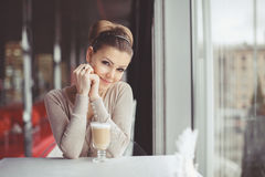 Young girl with a cup of coffee. Focus on the eyes. Pretty young woman sitting in a cafe with a cup of coffee latte royalty free stock image
