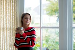 Young girl with cup of coffee stay near window. At home. Autumn season stock photo